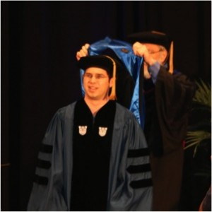 Kyle being hooded by one of his committee members